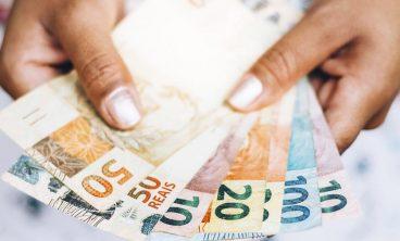 Mão segura dinheiro do pagamento do benefício emergencial