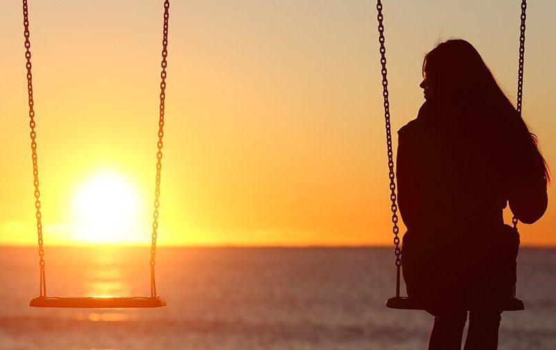 Mulher sozinha no balanço ao pôr do sol
