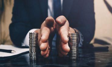 Mãos de homem executivo separam dois montes de moedas